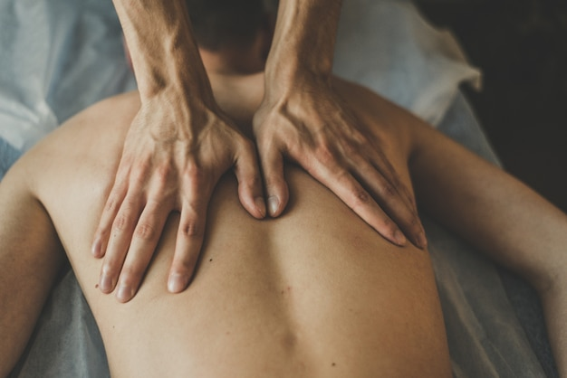 A man is given a back massage. relaxation on the massage table. beautiful tinted