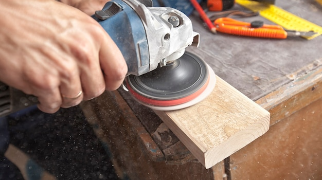 The man is grinding the wooden panel