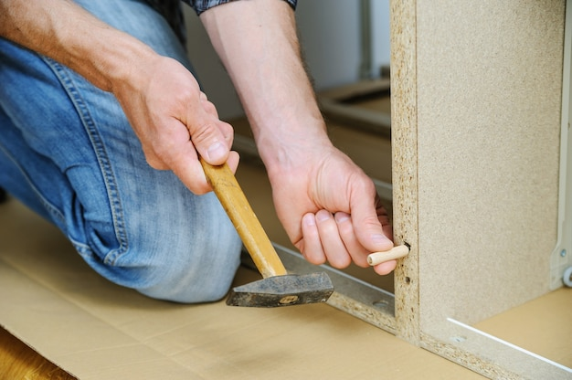 A man is hammering a wooden pin into a furniture board