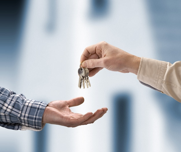 Man is handing a house key to a other man in the shape of the house.