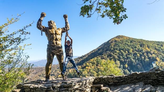 男は、ロシア、ソチのアフン山の背景にあるプロメテウスの彫刻にぶら下がっています。