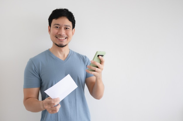 男は、スマートフォンと孤立した背景の請求書に満足しています。