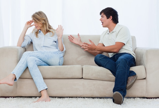 A man is having an argument with his girlfriend while sitting on a couch