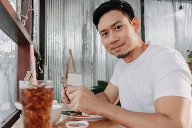 男は窓際に座っているレストランで昼食をとっている