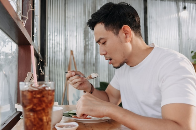 남자는 창가에 앉아 레스토랑에서 점심을 먹고 있다