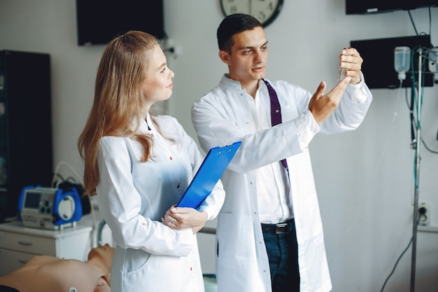 Мужчина держит флягу для анализа. медсестра с папкой в руках слушает врача. студенты в больничных халатах.