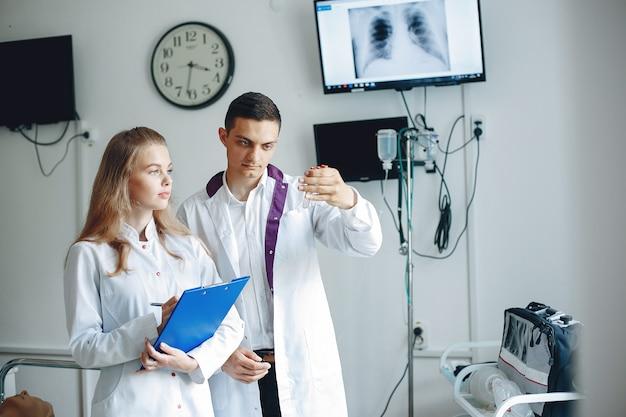 男は分析のためにフラスコを持っています。手にフォルダーを持った看護師は医者の話を聞きます。病院のガウンを着た学生。