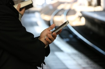 Man is holding a smartphone, background blurred railway.