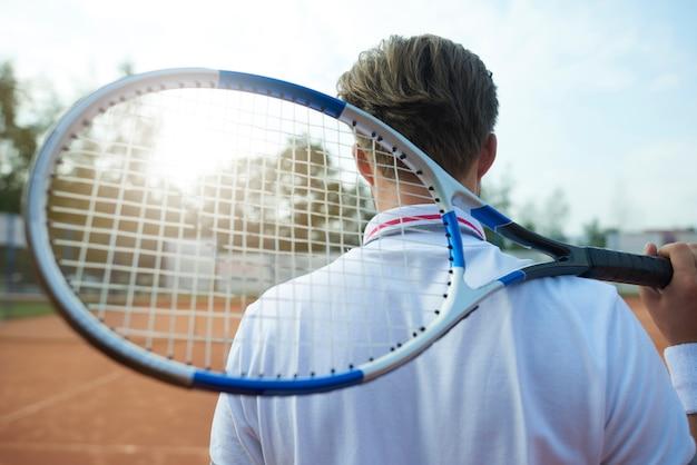 男はテニスラケットを持っています