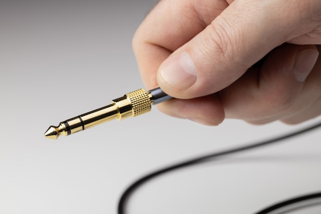 A man is holding an acoustic cable with a plug