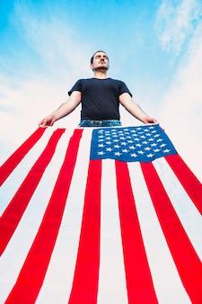 남자는 미국 미국 국기를 들고 있다. 애국심의 개념