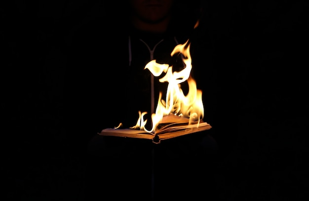 Man is holding burning book on fire at night. people don't like reading. intellectual problems.