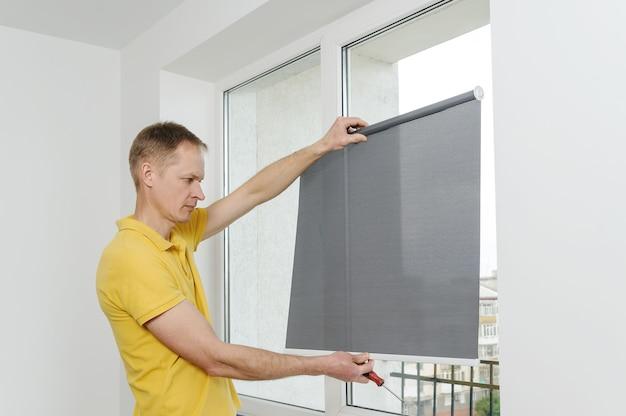 남자는 직물 창 블라인드 회색을 들고 있습니다.