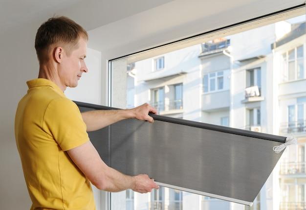 Мужчина держит серый слепой окна ткани.