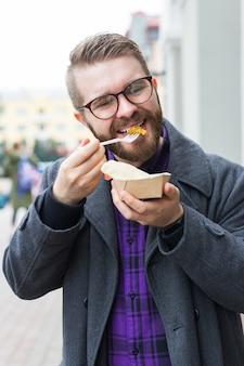 Мужчина держит сэндвич с фалафелем в бумажном пакете. концепция здоровой уличной еды, восточная кухня.