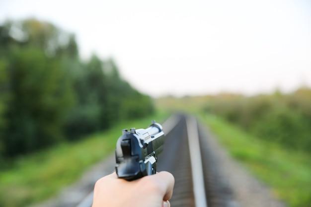 남자가 손에 총을 들고 있다. 범죄 개념 사진입니다. 배경에 철도 트랙입니다.