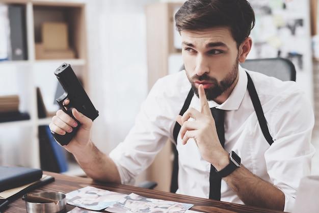 Man is holding gun and shushing while looking at photos.