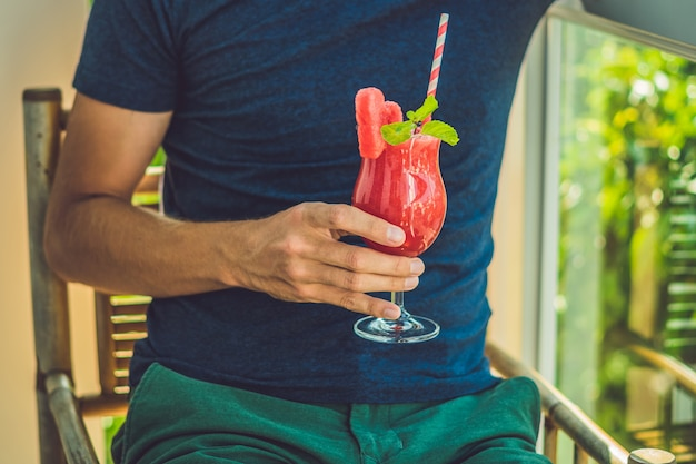 Man is holding healthy watermelon smoothie with mint and striped straws on a wood background