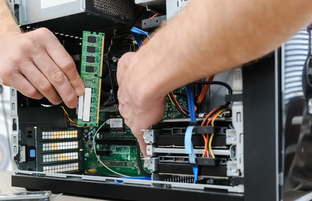 A man is holding a ram slot to upgrade of the computer.