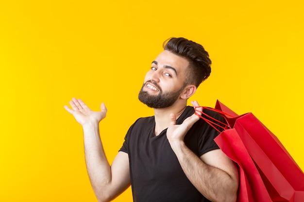 男は黄色の壁に赤い買い物袋を持っています
