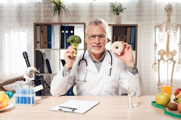 Man is holding and showing broccoli and donut.