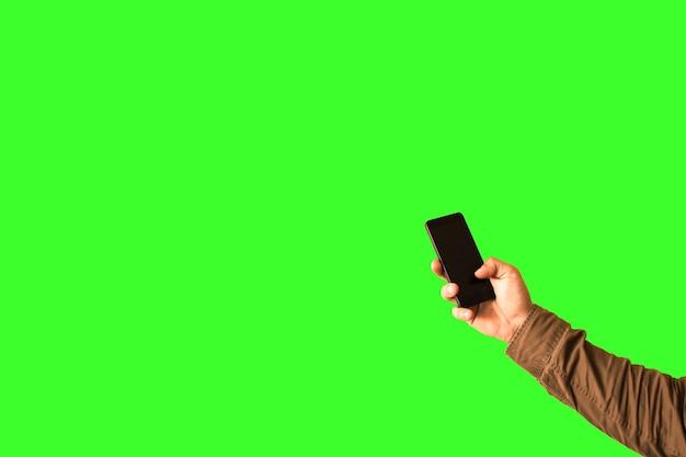 男は緑の背景に分離された手でスマートフォンを持っています。テクノロジーにはまっています。