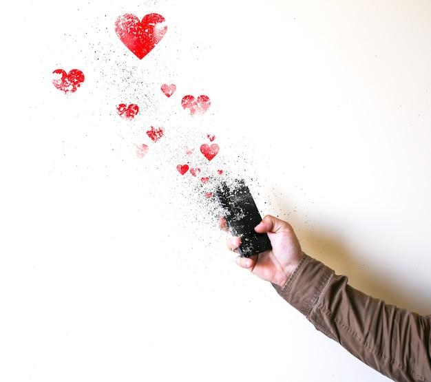 남자는 흰색 배경에 고립 된 손에 스마트폰을 들고 있다. 조각으로 떨어지는 스마트폰. 소셜 네트워크의 마음과 좋아요. 기술에 중독되었습니다.