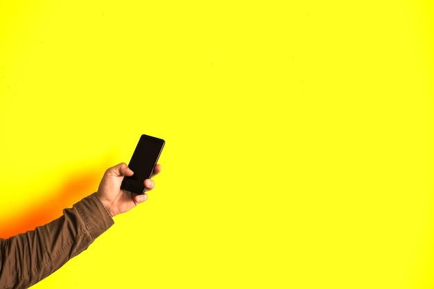 남자는 노란색 배경에 고립 된 손에 스마트폰을 들고 있다. 기술에 중독되었습니다.