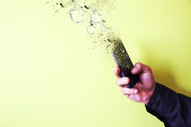 남자는 노란색 배경에 고립 된 손에 스마트폰을 들고 있다. 조각으로 떨어지는 스마트폰. 기술에 중독되었습니다.
