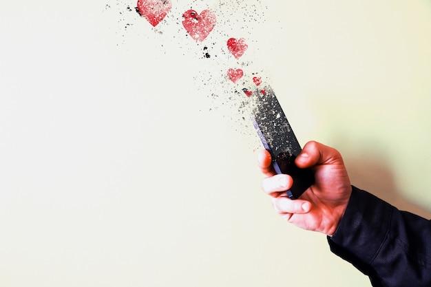 남자는 노란색 배경에 고립 된 손에 스마트폰을 들고 있다. 조각으로 떨어지는 스마트폰. 소셜 네트워크의 마음과 좋아요. 기술에 중독되었습니다.