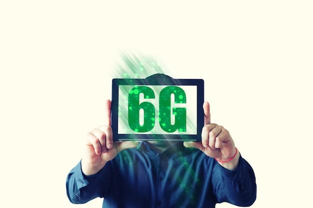 남자는 6g 표지판이 있는 테이블을 들고 있습니다. 새로운 인터넷 개념입니다. 전 세계의 연결을 커버합니다. 위험한 기술. 현대 개발.