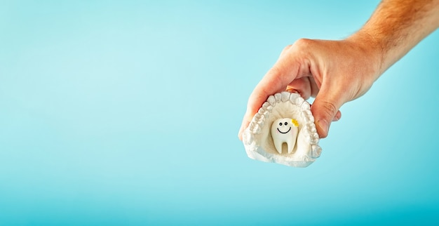 A man is holding a tooth on a blue background stomatology  concept dental health