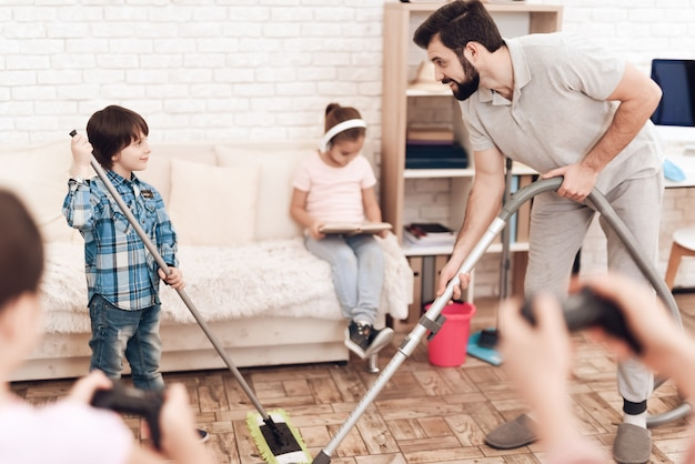Man is holding vacuum cleaner, and boy is holding a mop.