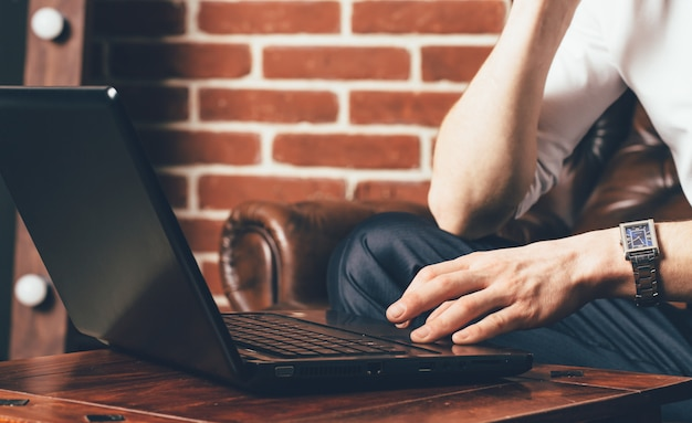 A man is holds his hand on the laptop's touchpad. he sits on a brown armchair in his own cabinet