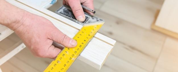 Man is installing the doors. ruler in hands. repair works. maintenance in the apartment.
