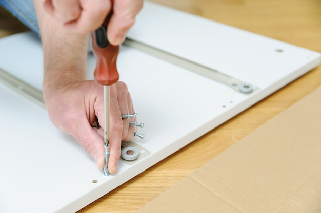 A man is installing joint connector bolts in the furniture board
