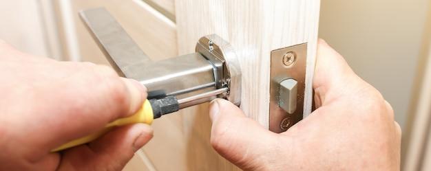 男はドアのハンドルを取り付けています。修理作業。アパートのメンテナンス。