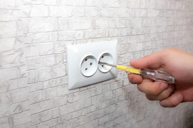 Мужчина устанавливает розетку. в квартире ремонтные работы по электричеству. реставрация в помещении.