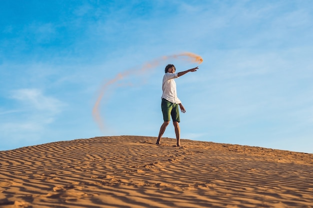 A man is kicking sand in a red desert. splash of anger concept.