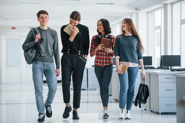 Man is laughing. group of young people walking in the office at their break time.
