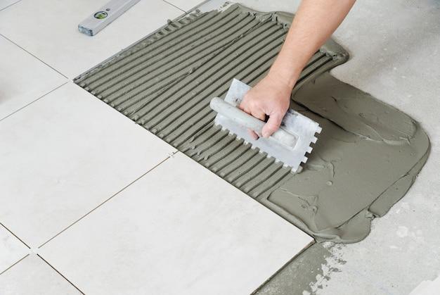 Человек укладывает керамическую плитку.
