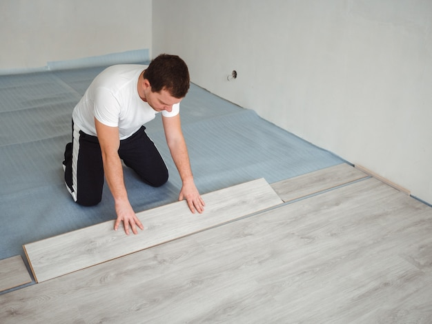 A man is laying laminate flooring. the repair process in the room