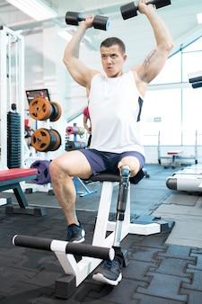 Man is lifting dumbbells