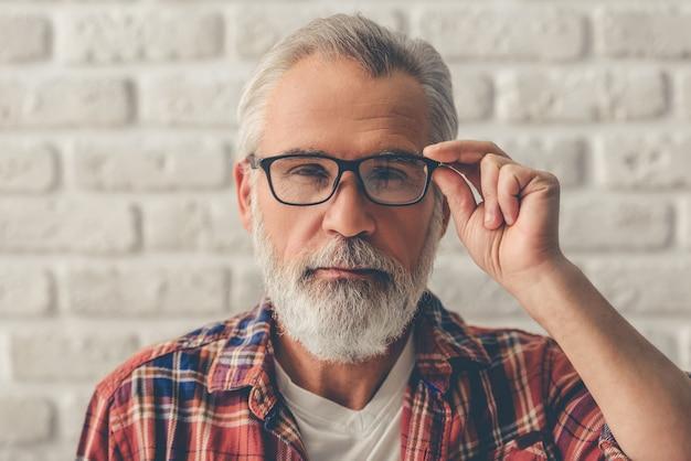 Человек смотрит на камеру на белом фоне кирпичной стены