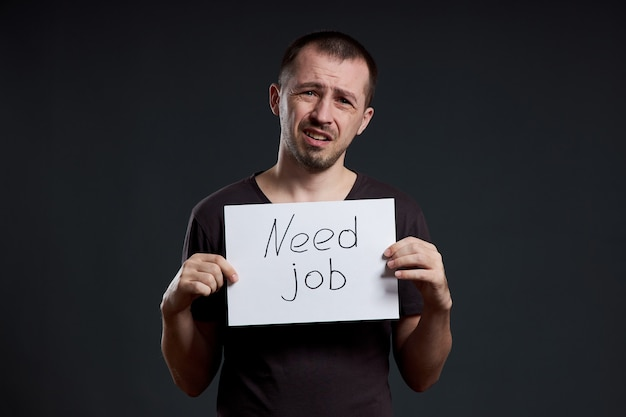 Мужчина ищет работу, безработицу и кризис. разные эмоции на лице, знак в руках
