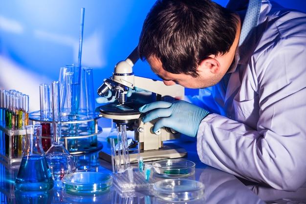 男は顕微鏡のガラスを調べて、研究を行っています