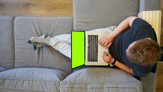 Человек лежит на диване дома с ноутбуком на коленях