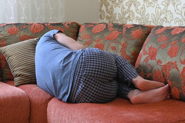 男はうつ病でソファに横たわっています。胎児の位置でソファーに横になっています。