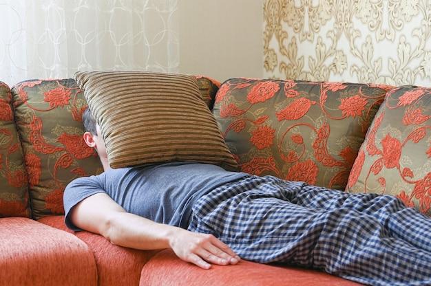 男はうつ病でソファに横たわっています。枕で覆われたソファーに横たわっています。