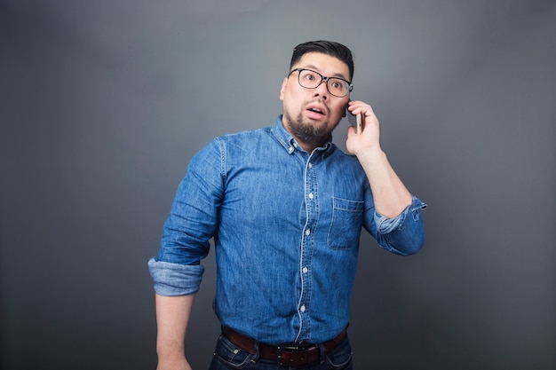 A man is making a phone call with a surprised expression.